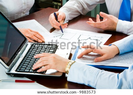 Image of three business people's hands at working meeting - stock photo