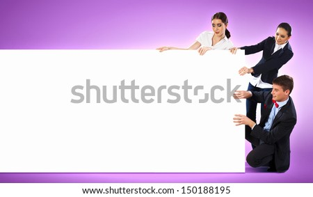 Image of three young people holding blank banner against purple background. Place for text