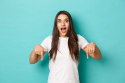 Image of thrilled beautiful girl looking happy and amazed, pointing fingers down, making announcement over blue background