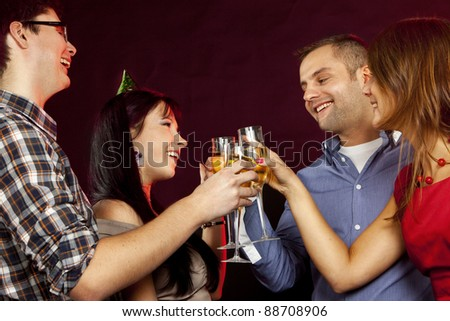 Image of toasting friends clinking glasses with champagne at New Year party