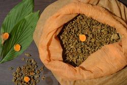 Image of turmeric (curcuma longa) granules in a pink bag with it's leaves rhizome and powder.