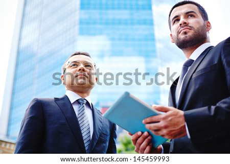 Image of two business guys in the urban environment, the younger one holding a touchpad