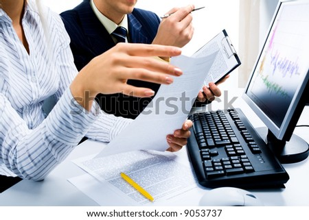 Image of two business partners discussing documents lying on the table with the keyboard and a monitor near by