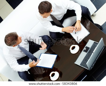Image of two business partners discussing work at meeting