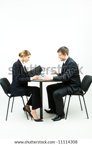 Image of two business people in suit sitting at the table on a white background