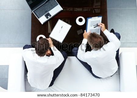 Image of two businessmen discussing work at meeting in office