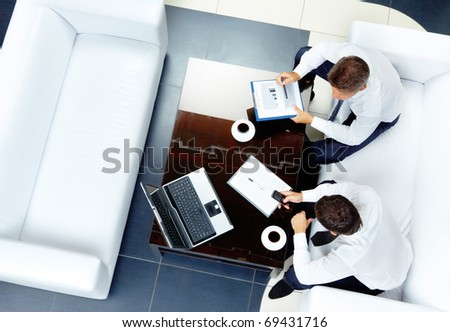 Image of two businessmen sitting on a white sofa