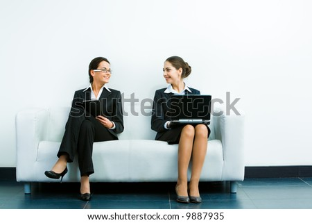 Image of two businesswomen wearing suits sitting on the white sofa smiling at each other on the background of wall