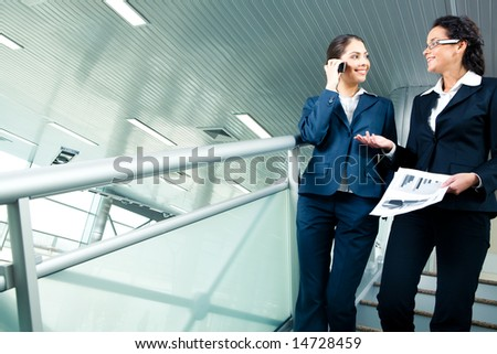 Image of two colleagues discussing new business project while going downstairs in office building