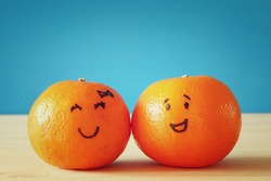 Image of two cute clementines with drawn smiley faces on wooden table. Best friend concept