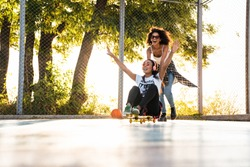 Image of two delighted african american girls having fun and riding skateboard together on playground