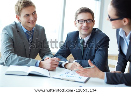 Image of two employees looking at businesswoman explaining her idea at meeting