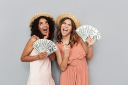 Image of two excited multiethnic women, caucasian and african american girls wearing summer clothing holding lots of money dollar bills isolated over gray background
