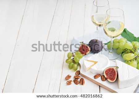 image of two glasses of wine, different cheeses , figs