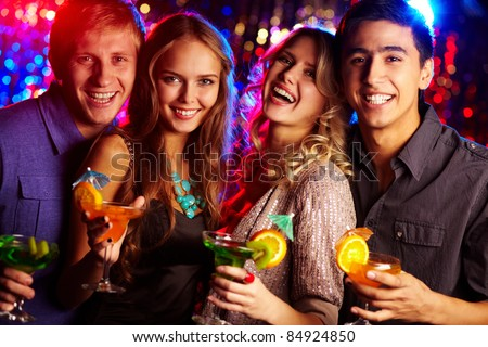 Image of two happy couples holding glasses of cocktails