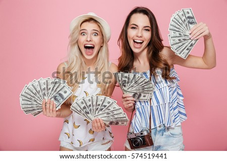Image of two happy emotional women standing isolated over pink background holding money.