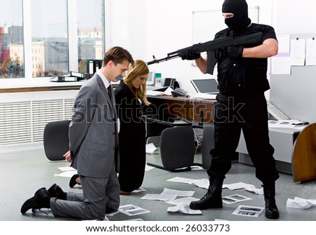 Image of two office workers standing on their knees in front of evil robber pointing gun at them