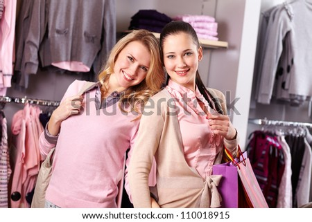 Image of two pretty girls looking at camera with smiles in department store