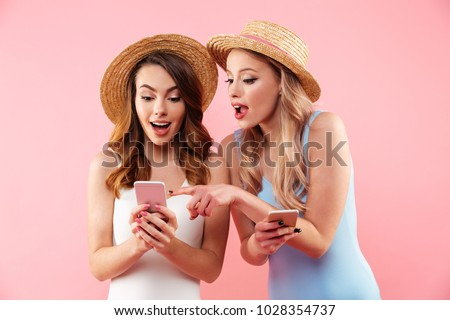 Image of two splendid women wearing one-piece swimsuits and straw hats browsing internet or using mobile phones isolated over pink background