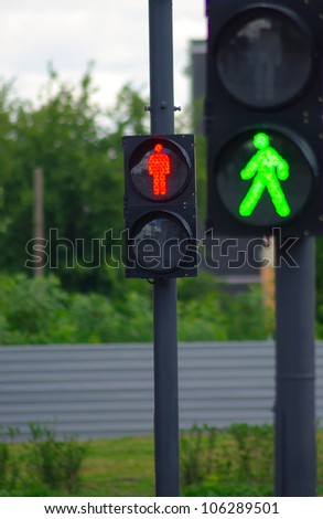 image of two traffic signals on the road on a background of trees