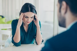 Image of two workers at a meeting in a restaurant. Young pretty exhausted businesswoman having headache because of problems at work.