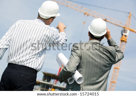 Image of two workers standing a back and showing at crane