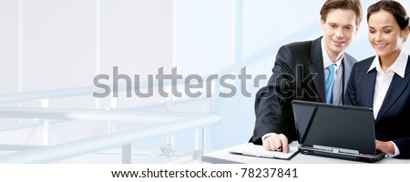 Image of two working people looking at laptop screen in office