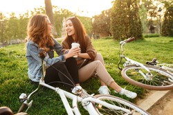 Image of two young beautiful women friends outdoors with bicycles in park.