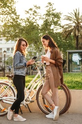Image of two young beautiful women friends outdoors with bicycles in park using mobile phone.