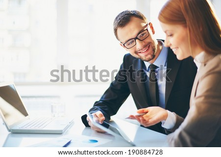 Image of two young business partners discussing plans or ideas at meeting