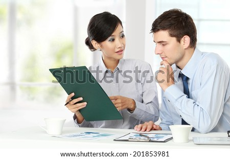 Image of two young business people at the meeting in the office