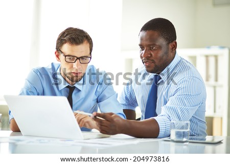 Image of two young businessmen using laptop and interacting at meeting