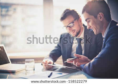 Image of two young businessmen using touchpad at meeting - Shutterstock ID 158522279