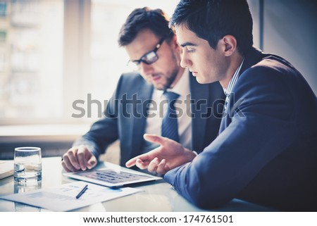 Image of two young businessmen using touchpad at meeting - Shutterstock ID 174761501