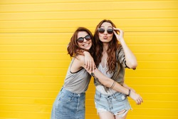 Image of two young happy women friends standing over yellow wall. Looking at camera blowing kisses.