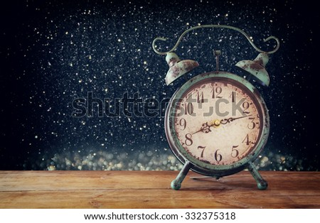 image of vintage alarm clock on wooden table in front of magical glitter silver and black lights background. retro filtered