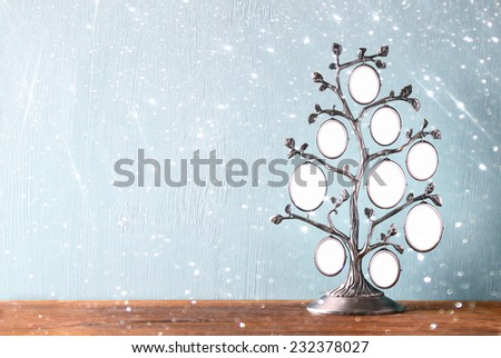 Image of vintage antique classical frame of family tree on wooden table and glitter lights background . filtered image