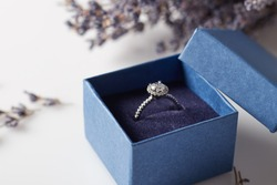 Image of wedding rings in a blue gift box. Beautiful rings in a blue box with delicate flowers.