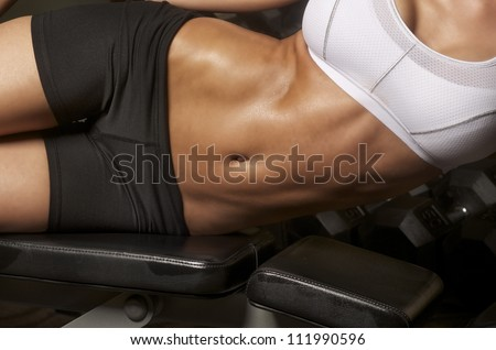 Image of well toned athletic young woman with tight defined abs in stomach