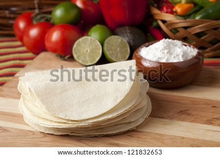 Image of wheat tortilla wrap with vegetables on wooden table
