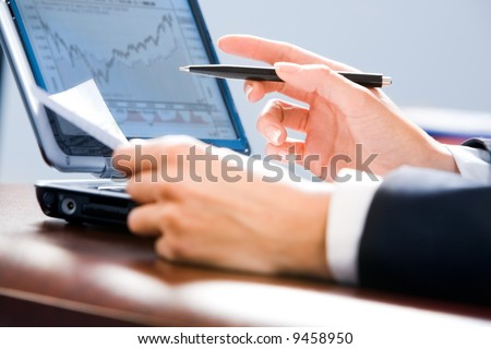 Image of white collar worker's hands holding a pen and paper