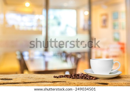 Photo of image of white cup of coffee on wooden board with Coffee shop blur background with bokeh.