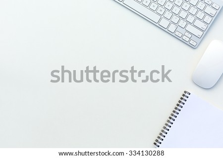 Image of White Office Table with Computer Keyboard Mouse and Paper Notepad Top View