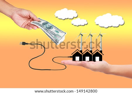 Image of wind turbine generating electricity with money in hand   on sky background.