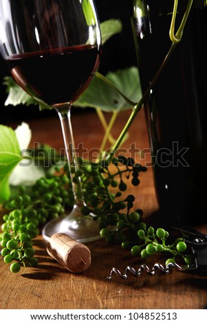 Image of wine goblet, bottle and cork on the wooden surface
