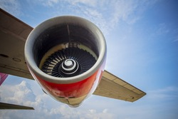 Image of wing and jet engine of airplane over blue sky.