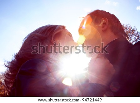 Image of woman and man kissing each other outside
