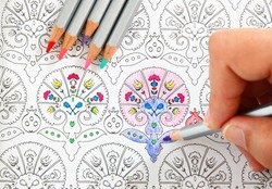 image of woman coloring, adult coloring book trend, for stress relief.  top view