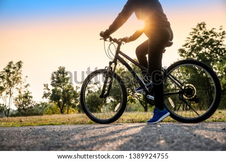 Image of woman early morning with riding bicycle outdoors. Looking a sunlight- Image