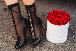 Image of woman's legs wearing black high heel shoes and socks next to white box with red roses